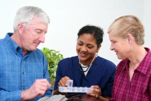 caregiver giving medicines to elderly seniors