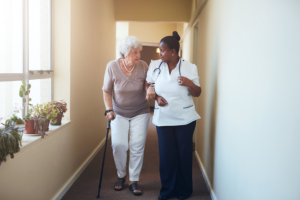 caregiver assisting senior woman in walking